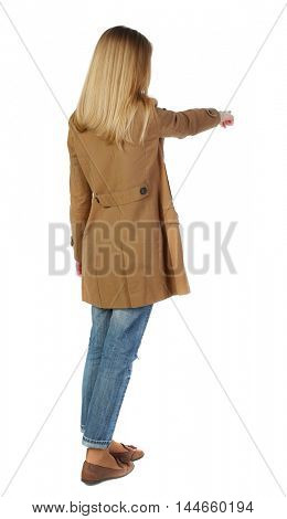 Back view of pointing young women in parka. blonde in a brown cloak, points a finger forward.