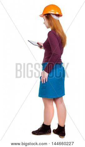 Backview of business woman in construction helmet stands and enjoys tablet or using a mobile phone. Red-haired woman engineer working on the tablet.