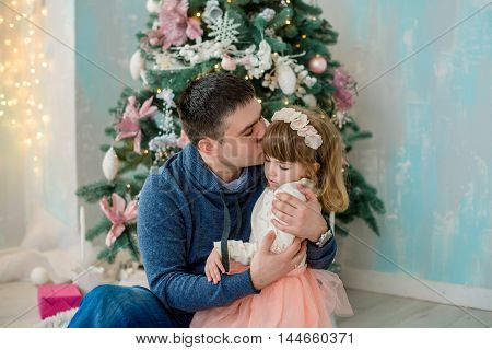 Happy father kissing his daughter in front of Christmas tree