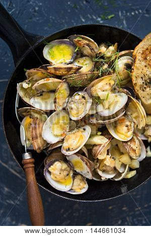 Steamed clams in a pan with fennel and butter