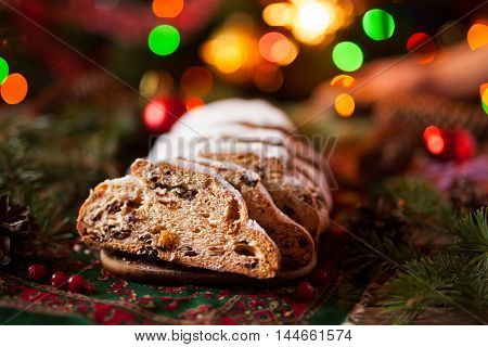 Traditional German Dresdner Christmas cake Stollen with Berries Nuts and Raising on a rustic wooden festive table. Holiday xmas celebration baking fruitcake. Atmospheric, cozy, romantic decorations.