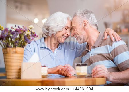 Love you deeply. Delighted loving senior couple bonding to each other and expressing feelings while resting at the table in the cafe