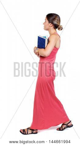 Girl comes with stack of books. side view. slender woman in a long red dress goes on the side carrying the book.