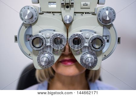 Female patient looking through phoropter during eye examination in ophthalmology clinic