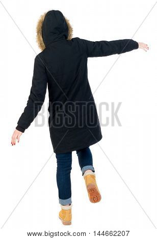 Back view woman in winter jacket Balances waving his arms. Standing young girl in parka. girl in warm winter jacket black balancing on one leg.