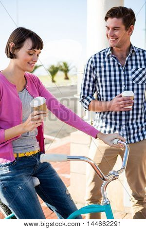 Happy couple with coffee cups having fun with a bicycle