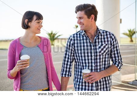 Happy couple with coffee cups walking together
