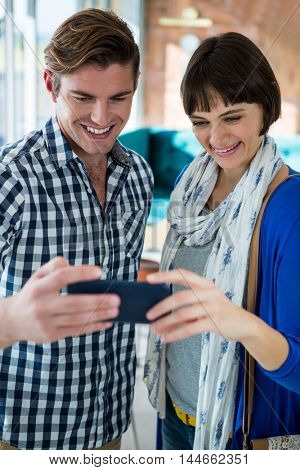 Smiling couple looking at the mobile phone in coffee shop