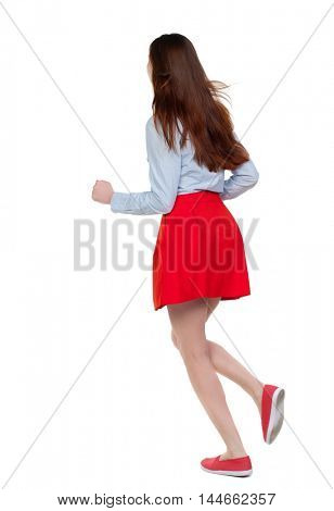 side view of running woman. beautiful girl in motion. Long-haired brunette in red skirt runs diagonally