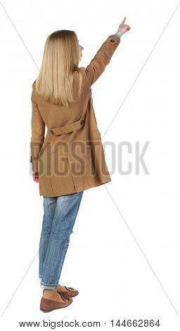 Back view of pointing young women in parka. blonde in a brown raincoat is pointing to the sky.
