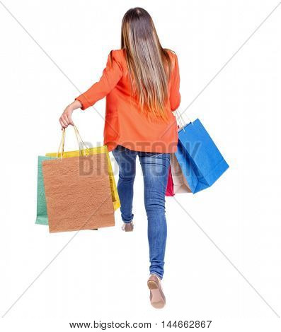 back view of a woman jumping with shopping bags. girl in a red jacket jumping with colored bags.