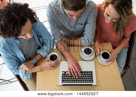 Three friends with coffee cups using a laptop in coffee shop