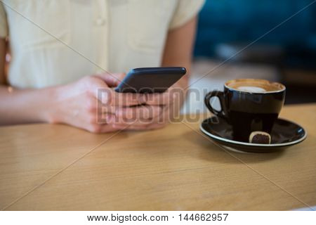 Mid section of woman using mobile phone with coffee cup on table in coffee shop