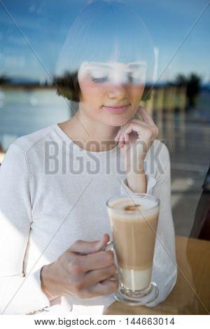 Thoughtful woman having milkshake in cafeteria