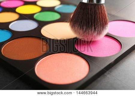 Colorful eye shadow palette with brush, closeup