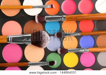 Colorful eye shadow palette with brushes, closeup