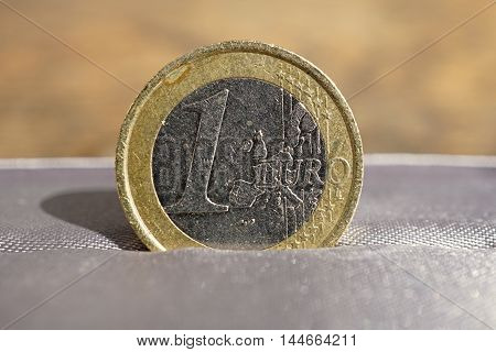 Macro detail of a silver and gold Euro coin placed in the gray luxurious jewelry gift box as a symbol of luxury and highly appreciated currency