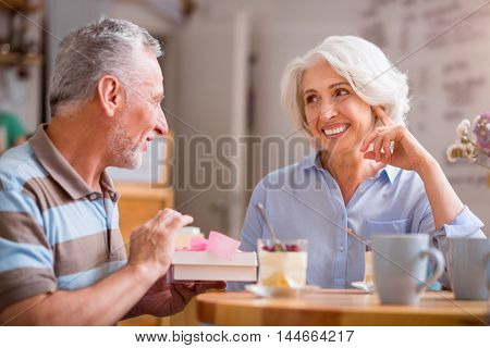 Pleasant surprise. Positive content senior loving couple smiling and sitting at the table while resting together