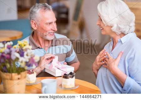 Want to make you happy. Cheerful senior smiling men giving present to his wife while resting in the cafe together