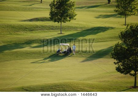 Golfer getting into golf cart on golf