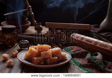 Arabic traditional gourmet dessert rahat lukum, lokum powdered with sugar, eastern candy. Turkish Still life. Holidays ramadan, seker bayram concept. Smoky hookah atmospheric.