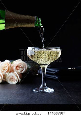 Pouring champagne into a glasses standing on the bar table. Women cocktail at a restaurant. Romantic evening and presented a bouquet of flowers. Black background, celebration time.