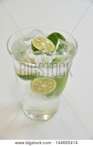Glass of green kumquat juice with cold ice on white background