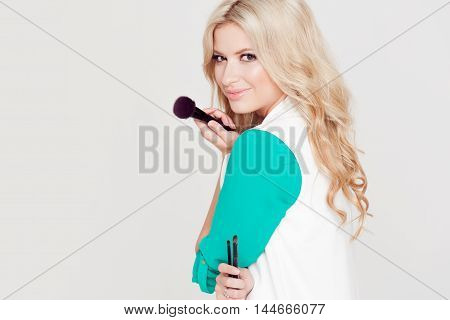 Portrait of a young girl artist with brush for makeup