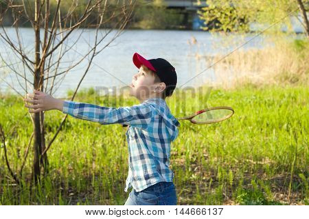 Boy playing badminton on the banks of the river in the spring
