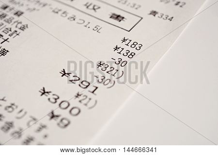 Macro detail of a Japanese paper receipt (white paper bill, sales slip) with a sum of several items and the additional tax as a symbol of market and accountancy in Japan