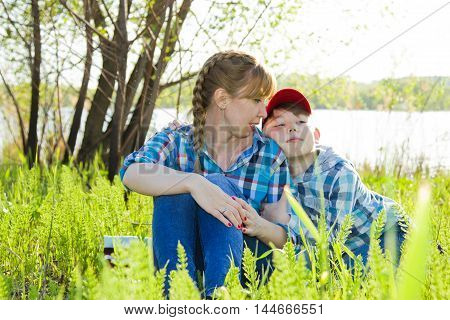 Mother and son sitting on the grass by the river