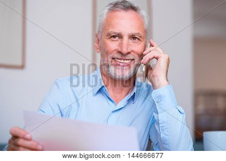 On the emotional wave. Cheerful delighted senior man smiling and sitting at the table while talking on cell phone
