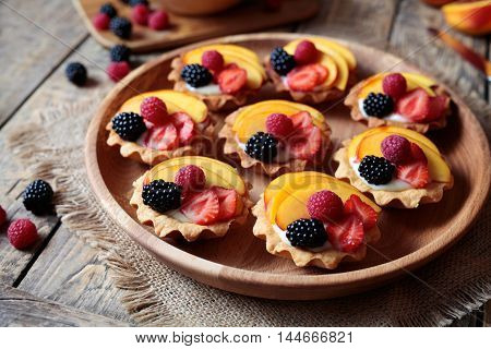Fruit dessert tartlets with vanilla custard and fresh raspberries, blackberry and peach served on wooden tray with baking forms, kitchenware on the old wooden table. Dark rustic style.