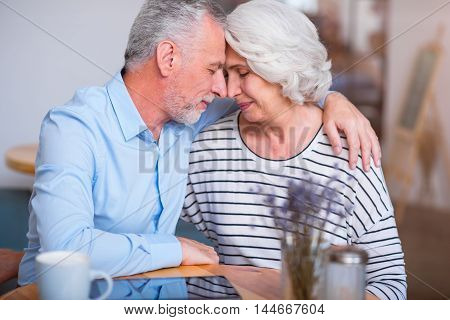 Eternal love. Pleasant delighted senior couple sitting at the table and bonding to each other while expressing love