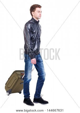 front view of walking man with suitcase. young man goes to side of a rolling travel bag on wheels