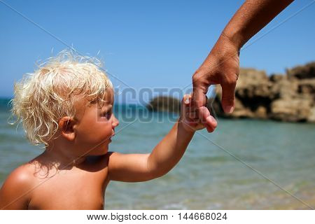 a father holds the hand of a small child on a blue background