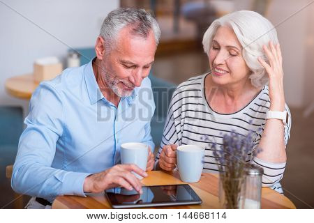 Modern way of life. Cheerful smiling senior couple drinking tea and using tablet while resting in the cafe