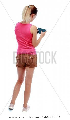 back view of standing young beautiful woman using a mobile phone or tablet computer. Isolated over white background. Sport blond in brown shorts playing on the tablet.