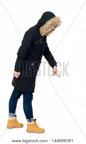 Back view of pointing young women in parka. girl in warm winter jacket is black with cancer and is pointing down.