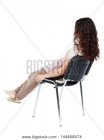 back view of young beautiful woman sitting on chair. Isolated over white background. Long-haired curly girl sitting on a chair reclining.