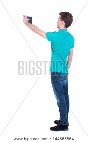 back view of standing business man photographing a phone or tablet. Curly man in a turquoise sweater standing sideways on making selfie smartphone.
