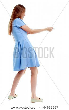 back view of standing girl pulling a rope from the top or cling to something. Isolated over white background. Skinny girl in a blue dress and pulls the rope.