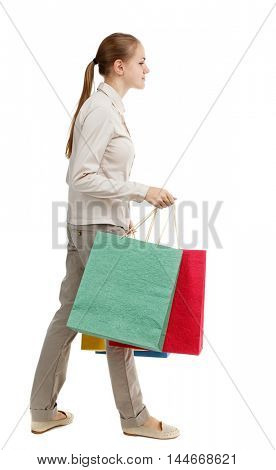 side view of going woman with shopping bags . beautiful girl in motion. Isolated over white background. Skinny girl in white jeans passes in colorful packages.