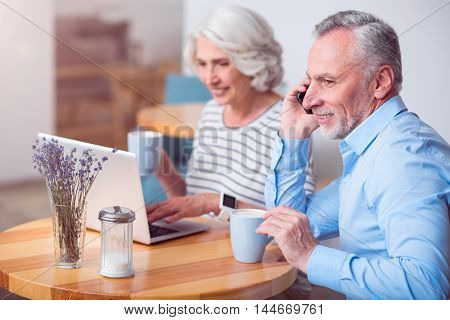 Modern old generation. Cheerful smiling man talking on cell phone and his wife using laptop while resting in the cafe together