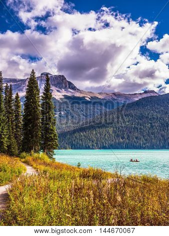 The Emerald Lake  in the Rocky Mountains of Canada. Group of tourists crosses the lake in a rowboat