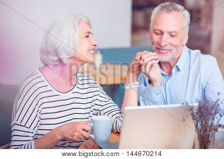 My lady. Positive delighted senior loving couple sitting at the table and expressing loving while using laptop