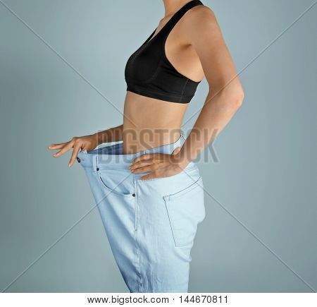 Girl in huge pants on grey background