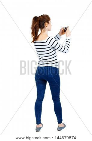 back view of standing young beautiful woman using a mobile phone. girl watching. Girl in striped sweater looking to the mobile phone.
