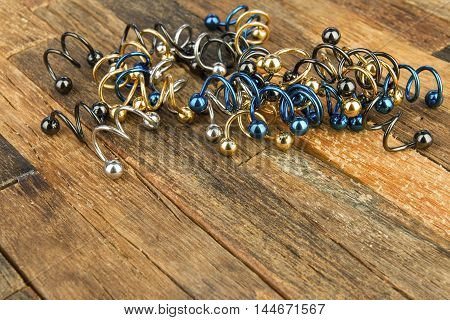 Jewelry for piercing on wooden background. Stock Image macro.