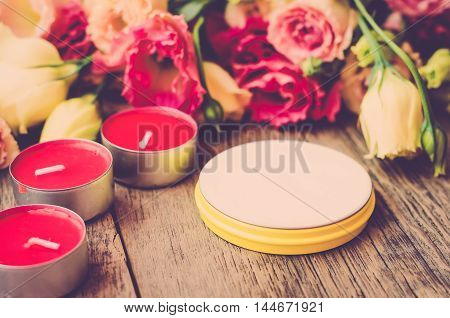 Open a jar of cream on a wooden table on a background of beautiful flowers next to the scented candles. Children cream in a jar (vintage)